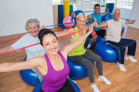 Portrait of fit people on fitness balls exercising with resistance bands in gym