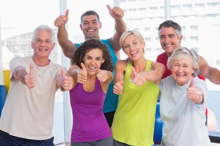 group of young people: Portrait of happy friends gesturing thumbs up in fitness club