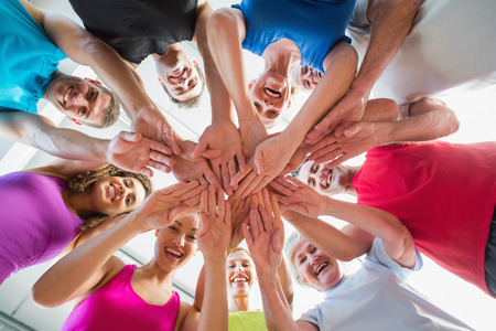 Low angle view of fit people stacking hands at health club Imagens