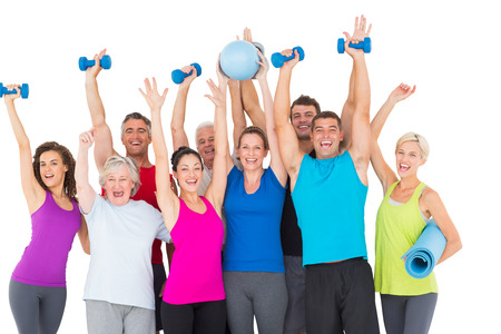 Portrait of excited people with exercise equipment raising hands against white background photo