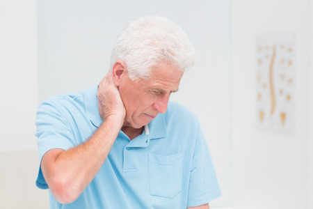 senior man on a neck pain: Senior man suffering from neck ache in clinic