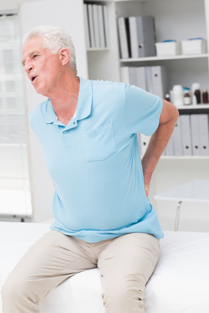 pain: Senior man screaming due to back pain in clinic