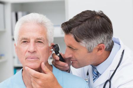 남성 의사 수석 환자 귀에 otoscope 클리닉에서 검사