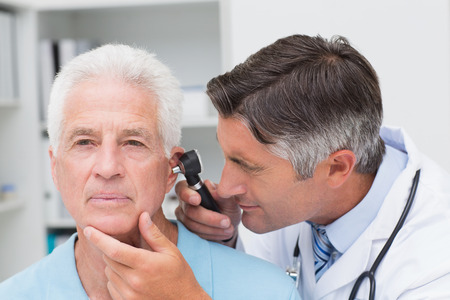 Male doctor examining senior patients ear with otoscope in clinic