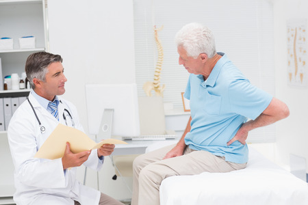 examining: Male doctor discussing reports with senior patient suffering from back pain in clinic