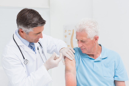 man arm: Male doctor injecting senior patient in clinic
