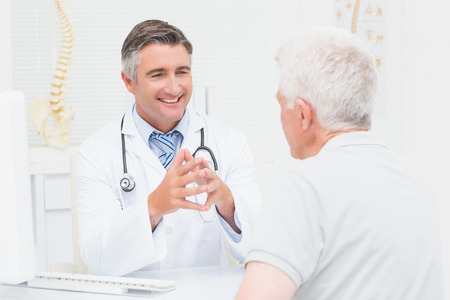 male senior adults: Male orthopedic doctor discussing with senior patient in clinic Stock Photo