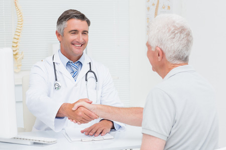 Happy male doctor shaking hands with senior patient in clinc