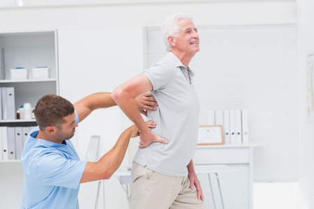 Physiotherapist giving back massage to senior male patient in clinic