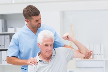 enfermera con paciente: Fisioterapeuta dar terapia f�sica para hombre de alto nivel en la cl�nica Foto de archivo