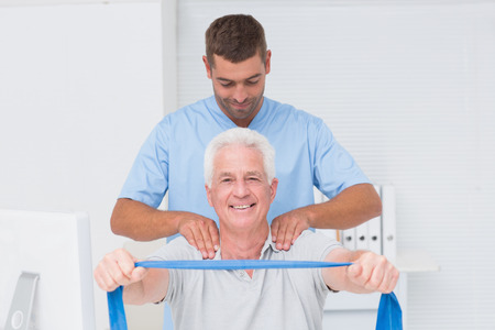 Male physiotherapist assisting senior patient in exercising with resistance band at clinic Stock Photo