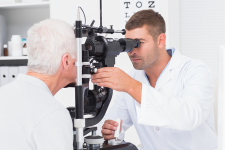 eyes: Male optometrist examining senior mans eyes through slit lamp in clinic