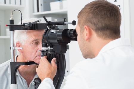 yeux: Homme opticien examen hauts patients yeux � travers la lampe � fente � la clinique Banque d'images