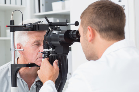 Male optician examining senior patients eyes through slit lamp in clinic