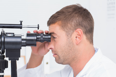 slit: Side view of optician using slit lamp in clinic