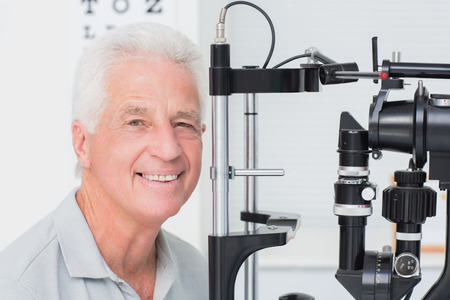 slit: Portrait of happy senior man in front of slit lamp at clinic Stock Photo