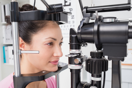 slit: Beautiful female patient looking into slit lamp at clinic