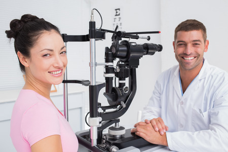 slit: Portrait of happy optician and female patient with slit lamp in clinic