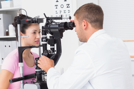 examined: Young female patient being examined by optician in clinic