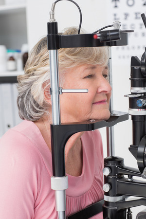 slit: Beautiful senior patient looking into slit lamp at clinic Stock Photo