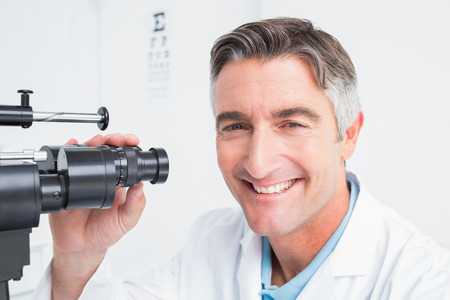 slit: Portrait of happy optician using slit lamp in clinic
