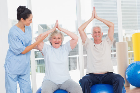 assisted: Portrait of senior couple on exercis ball being assisted by trainer in gym