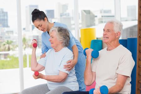 actividad fisica: instructor de sexo femenino joven que asiste a la mujer mayor en el levantamiento de pesas por el hombre en el gimnasio
