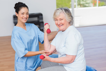 Portrait de monitrice aider femme âgée dans la levée des haltères au gymnase