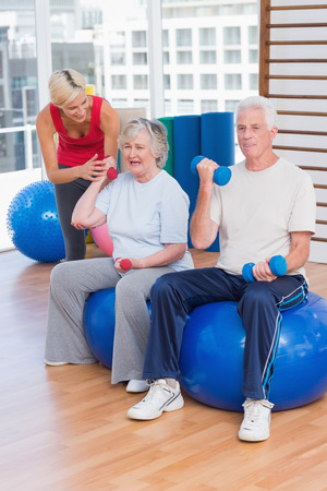 motivating: Female trainer motivating senior couple in lifting dumbbells at gym Stock Photo