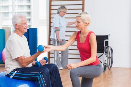 actividad fisica: Entrenadora asistir hombre mayor en el ejercicio de pesas mientras que la mujer con muletas en el fondo en el gimnasio