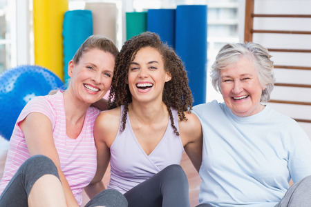 health woman: Portrait of happy female friends sitting together in gym