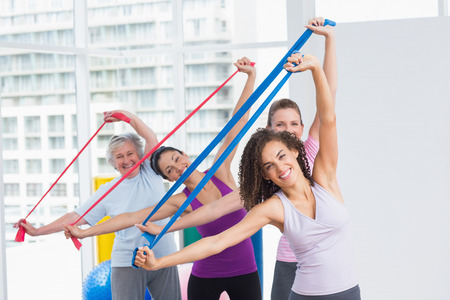 resistance: Portrait of happy female friends exercising with resistance bands in gym