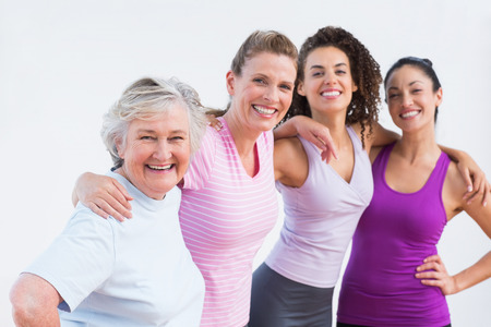 Portrait of happy friends standing arms around in fitness studio