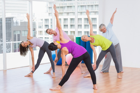 guiding: Full length of instructor guiding friends in stretching exercise at gym
