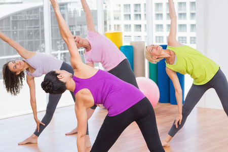 guiding: Female instructor guiding friends in stretching exercise at gym Stock Photo