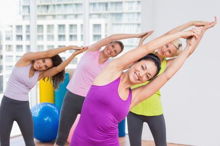mujeres maduras: Retrato de la mujer feliz practicando ejercicios de estiramiento en el gimnasio