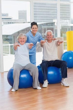 medicine ball: Portrait of senior couple on exercis ball with trainer in gym