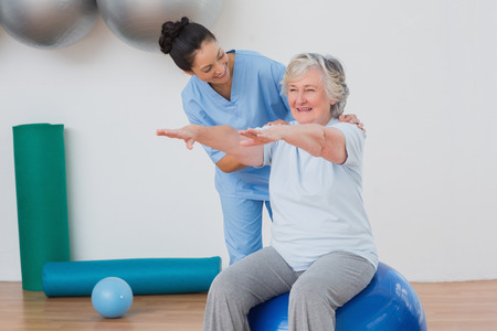 Happy instructor assisting senior woman in exercising at gym Stock Photo