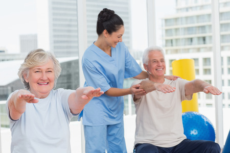 Happy young trainer assisting senior couple in exercising at gym photo