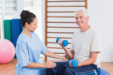 Female instructor assisting senior man in lifting dumbbells at gym photo
