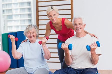 Portrait of happy female trainer with senior couple in fitness studio photo