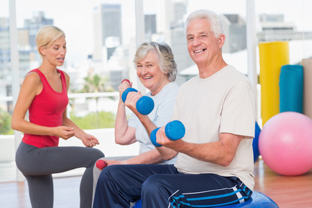 Portrait of happy senior couple lifting dumbbells while instructor guiding them in gym photo