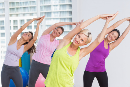 fit woman: Portrait of happy women practicing stretching exercise at fitness studio