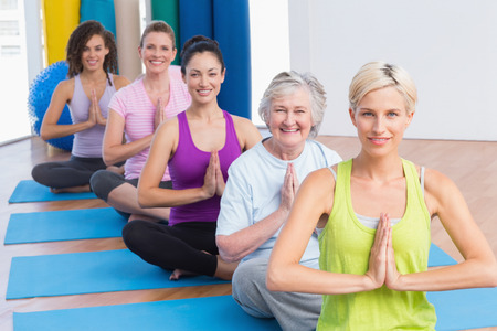 Portrait of happy fit women meditating with hands joined during fitness class photo