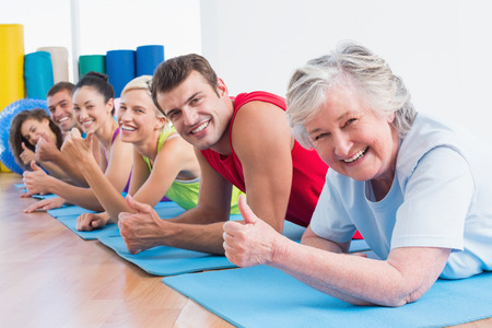 Portrait of happy senior woman with friends gesturing thumbs up while lying on exercise mats at gym photo