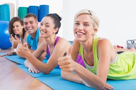 Portrait of happy woman with friends gesturing thumbs up while lying on exercise mats at gym photo