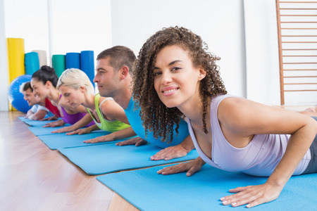 Portrait of woman with friends practicing push-ups at fitness studio photo