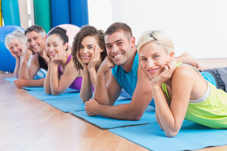 Portrait of fit people relaxing on exercise mats at fitness studio photo