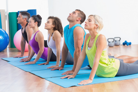 Men and women doing yoga stretch in gym class