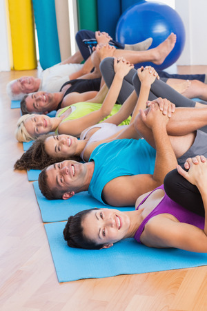 Portrait of happy people stretching legs in yoga class photo